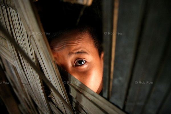 Many of the children do not go to school at all. This boy hides between the flimsy wall separating two classrooms while other children study.<br /> <br /> Since early 2006, some 2,000 refugees have fled from Myanmar into Thailand. They join 140,000 previous arrivals, many of whom have been living in refugee camps in northern and western Thailand for as long as 20 years.