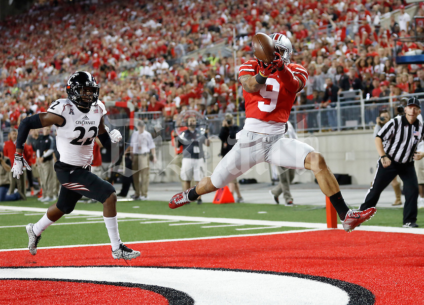 Ohio State Buckeyes wide receiver Devin Smith (9) catches a touchdown pass behind Cincinnati Bearcats safety Zach Edwards (22) during the fourth quarter of the NCAA football game at Ohio Stadium in Columbus on Sept. 27, 2014. (Adam Cairns / The Columbus Dispatch)