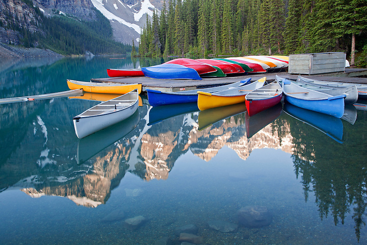 Mountains surrounding Moraine Lake reflect into calm waters as canoes rest on the dock and in the lake, Banff National Park, Alberta, Canada<br /> <br /> Third Place, &quot;Outdoor Fun and Adventure Category&quot; in the 2013 Outdoor Writers Association of America &quot;Excellence in Craft&quot; awards
