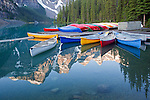 Mountains surrounding Moraine Lake reflect into calm waters as canoes rest on the dock and in the lake, Banff National Park, Alberta, Canada<br />