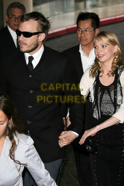 HEATH LEDGER & MICHELLE WILLIAMS.78th Annual Academy Award Nominees' Luncheon - Arrivals held at the Beverly Hilton Hotel, Beverly Hills, California, USA..February 13th, 2006.Photo: Zach Lipp/AdMedia/Capital Pictures.Ref: ZL/ADM.half length celebrity couple holding hands sunglasses shades black white.www.capitalpictures.com.sales@capitalpictures.com.© Capital Pictures.