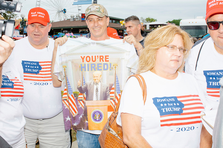 """People wearing """"Iowans for Trump"""" shirts gathered near the Political Soapbox at the Iowa State Fair in Des, Moines, Iowa, on Sun., Aug. 11, 2019."""