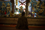 © Joel Goodman . 18 May 2013 . Gita Bhavan Hindu Temple , Withington Road , Whalley Range , Manchester . A woman preys in front of a statue of Ganesha at the temple . Commemorative service to celebrate the handover of the Green Kumbh Yatra (green journey pot or environmental pilgrimage) at the Gita Bhavan Hindu Temple in Manchester . The pot has travelled to the Maha Kumbh Mela , Kenya , Nepal and the Western Wall in Jerusalem along the way . At every place of rest an environmental action must be taken to reflect the pot's environmental significance . It's due to travel to Leicester and feature in an outdoor procession in London on 24th May 2013 . Photo credit : Joel Goodman