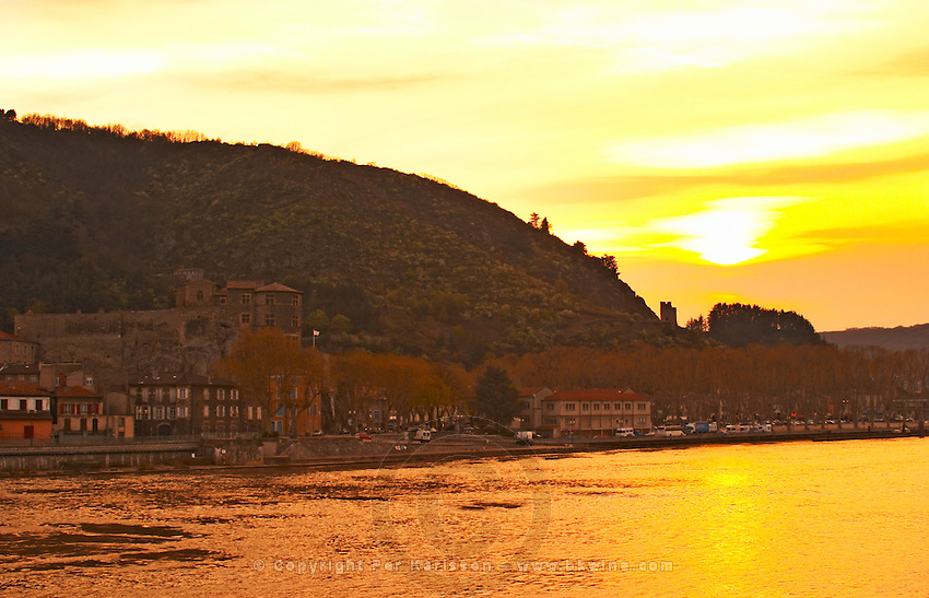 The town Tournon, across the Rhone river from Tain l'Hermitage with the Chateau de Tournon in the setting sun, Tournon-sur-Rhone, Ardeche Ardèche, France, Europe