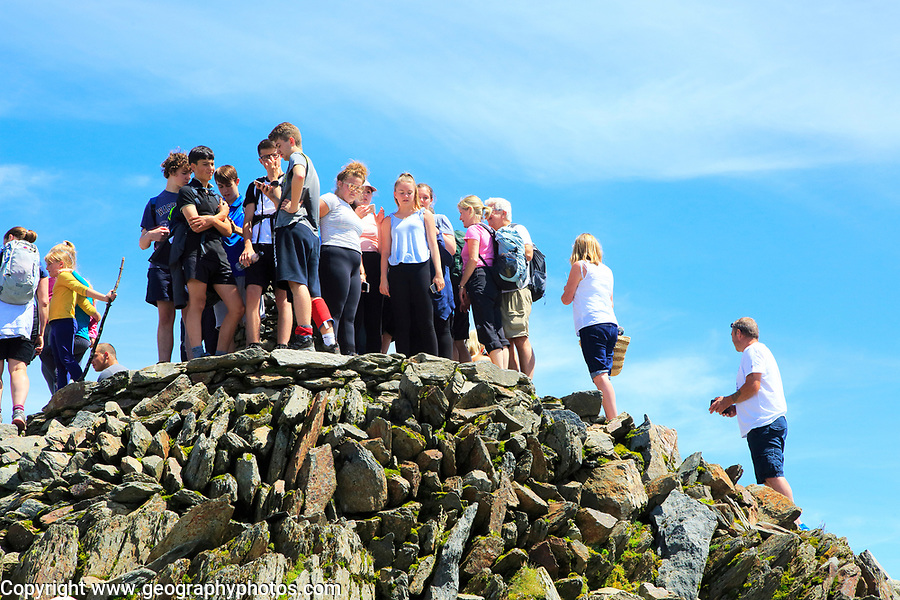 Walkers crowd onto the summit point, Mount Snowdon, Gwynedd, Snowdonia, north Wales, UK