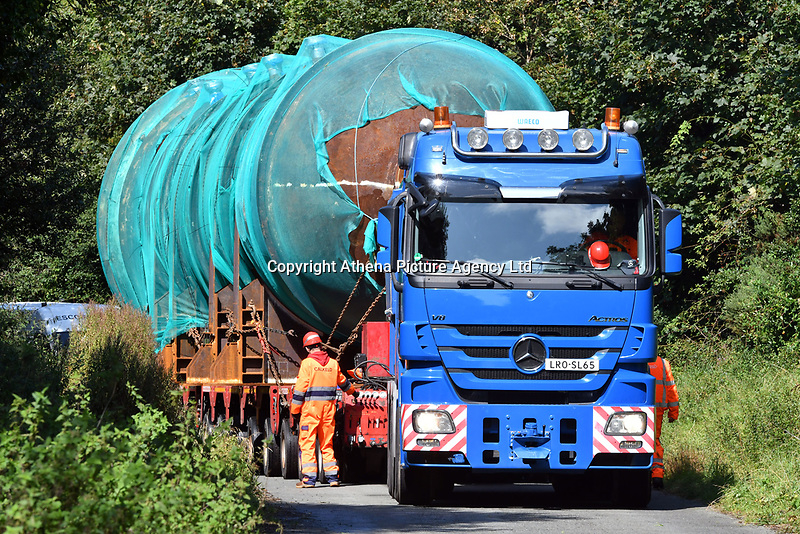 Pictured: 200 ton column being transported by road<br /> Re: A large dismantled section of an oil refinery has been taken away by road ready to be shipped and rebuilt in Pakistan.<br /> Policing units escorted it on the five-hour journey from the former Murco site in Milford Haven, Pembrokeshire, to Gelliswick Bay on Tuesday.<br /> About 600 people once worked there but it closed in November 2014.<br /> It is now a storage facility, with about 100 people carrying out decommissioning work over two years.<br /> The load will remain on the beach overnight before being taken away by barge on 6 September.<br /> Decommissioning is set to be completed in Autumn 2018, with the whole refinery being re-assembled in Pakistan.