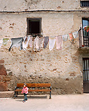 SPAIN, Ezcaray, La Rioja, girl walking in front of bench, clothes hanging on clothesline
