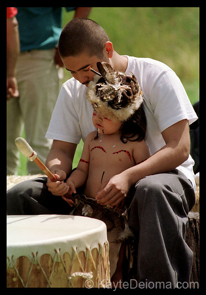 Chumash teen helps his pre-K little brother in traditional regalia drum on a skin drum at a gathering at Satwiwa American Indian Cultural Center in the Santa Monica Mountains Recreation Area near Los Angeles, CA