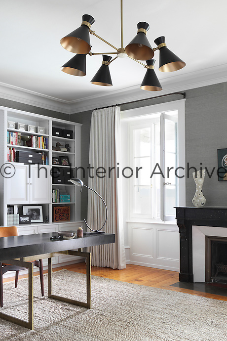 Among the 1950s style furniture in the study is a six lamped light fitting suspended from the ceiling, its metallic finish ties neatly with the metal legs of the desk below