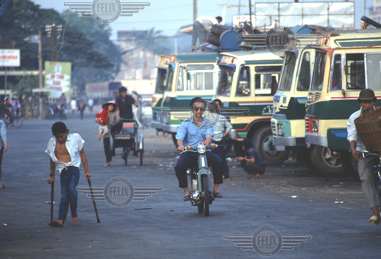 Vietnam, No Chi Minh City..Transport. Crippled man passing buses in the long distance bus station..©Mark Henley