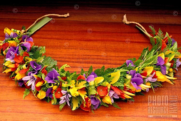 A beautiful purple, yellow and red haku lei (Hawaiian floral headpiece) on a koa background.
