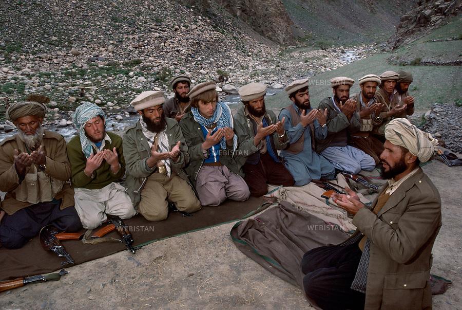Afghanistan. Pandjchir valley. Mai 1985. A group of Massoud mujaheddin in prayer. 2nd and 4th left: Aziz-Odin and Islam-Odin, two Russian and Ukranian renegades of the Soviet army. They live and fight alongside the mujaheddin.<br /> <br /> Afghanistan. Vall&eacute;e du Pandjchir. Mai 1985. Un groupe de moudjahiddine de Massoud en pri&egrave;re. A gauche, en 2e et 4e position : Aziz-Odin et Islam-Odin, deux soldats russe et ukrainien transfuges de l'arm&eacute;e sovi&eacute;tique. Ils vivent et luttent aux c&ocirc;t&eacute;s des moudjahiddine et sont convertis.