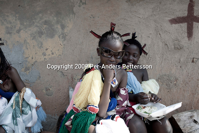 LUDZIDZINI, SWAZILAND - AUGUST 31: Unidentified girls eat before a traditional Reed dance ceremony at the Royal Palace on August 31, 2009, in Ludzidzini, Swaziland. About 80.000 virgins from all over the country attended this yearly event, which goes on for a week and which is the biggest in Swazi culture. Many of the girls stayed in tents and slept on the ground. It was founded to celebrate the beauty of Swazi women and girls. King Mswati III, and absolute monarch, was born in 1968 and he has 14 wives and many children. The king danced with his men in front of the 80.000 girls. Many of the girls hope to get noticed by the king and to be chosen as a future wife, a ticket from poverty and into a life of privilege and luxury. The country is one of the poorest in the world and it is struggling with a high prevalence of HIV-Aids and severe poverty. (Photo by: Per-Anders Pettersson)...