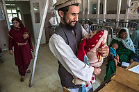 KABUL, AFGHANISTAN - SEPTEMBER 21: An Afghan man holds his child as he waits for hi smalnourished child to be seen, at the Indira Gandhi Children Hospital on September 21, 2013 in Kabul, Afghanistan.