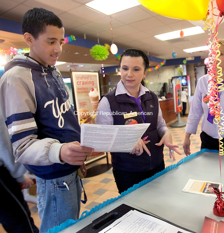 WATERBURY, CT. 19 April 2011-041911SV11--From left, Sebastian Olavarria, 17 of Waterbury takes an application from Evelyn Soto, store manager, at McDonalds on Reidville Drive in Waterbury Tuesday. The restaurant was participating in company's National Hiring Day. The company plans to hire 50,000 people nationwide, 1,300 in Conn. <br /> Steven Valenti Republican-American