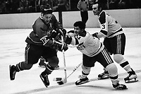 Seals vs Montreal Canadiens 1970, Seals Wayne Muloin, and Harry Howell, battle Fran Huck. (photo by Ron Riesterer)