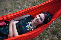 "Romania. Iași County. Iasi. A stylish and smiling woman is lying in a red hamac during the festival "" Street Delivery. Global Warning"" which takes place in the Pogor garden near the museum ""Vasile Pogor"", a literary history museum which is part of the Iași Romanian Literature Museum ( Muzeul Literaturii Romane Iasi). Iași (also referred to as Iasi, Jassy or Iassy) is the largest city in eastern Romania and the seat of Iași County. Located in the Moldavia region, Iași has traditionally been one of the leading centres of Romanian social life. The city was the capital of the Principality of Moldavia from 1564 to 1859, then of the United Principalities from 1859 to 1862, and the capital of Romania from 1916 to 1918. 13.06.15 © 2015 Didier Ruef"