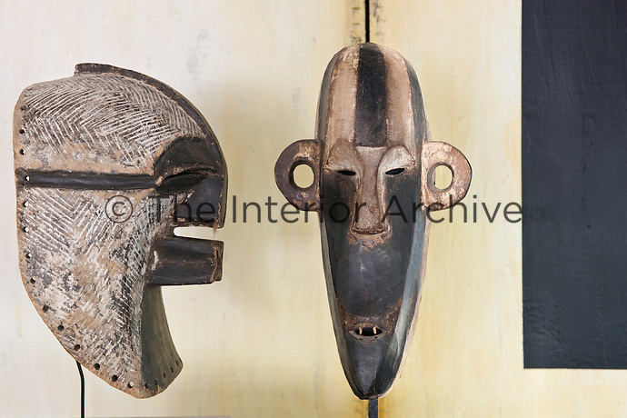 Different shapes and techniques for a pair of Congo masks, part of a larger collection displayed throughout the house