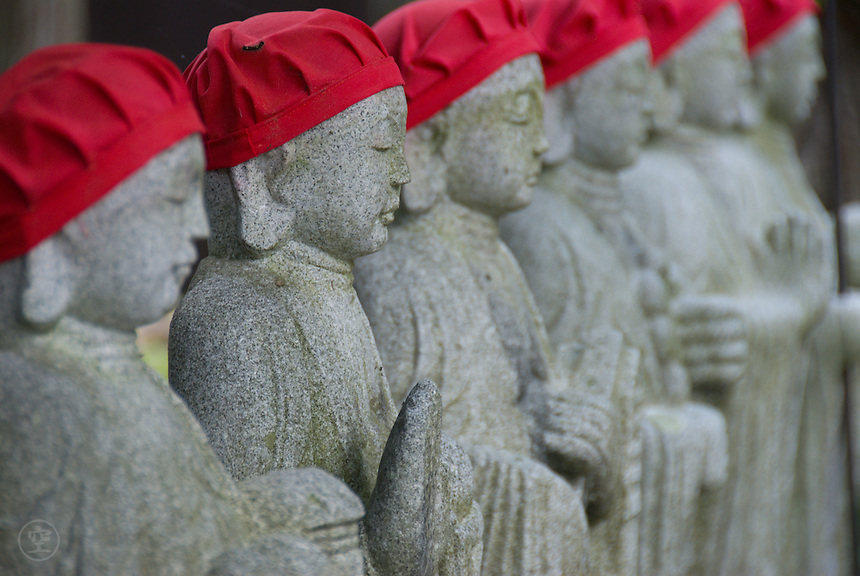 A line of Buddshist Jizo statues, in red hats, at a Buddhist temple at Narai, Kiso Valley, Nagano, Japan. June 8 2008