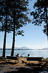 A woman and her dog look out over Lake Ewauna from Veterans Park, Klamath Falls, Oregon