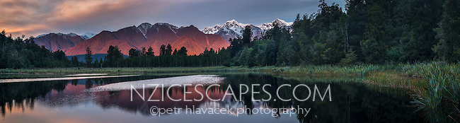 Winter dusk over Aoraki, Mt. Cook and Mt. Tasman of  Southern Alps, reflecting in Lake Matheson, Westland Tai Poutini National Park, West Coast, UNESCO World Heritage Area, South Westland, New Zealand, NZ