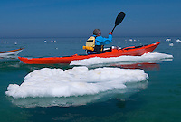 A sea kayaker paddles through ice floating in Lake Superior at Pictured Rocks National Lakeshore near Munising, Michigan.