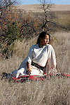 A young Native American Indian Woman sitting on a red blanket
