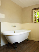 The free-standing bath sits comfortably in a panelled corner of the bathroom