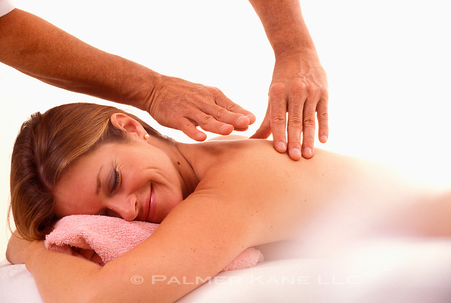 Masseur relaxes muscles in client's back