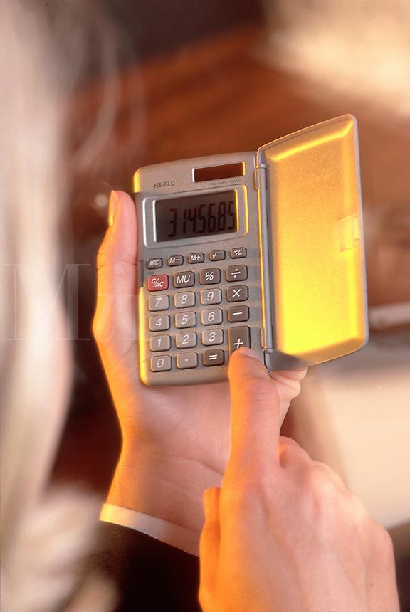 Hands using a calculator.