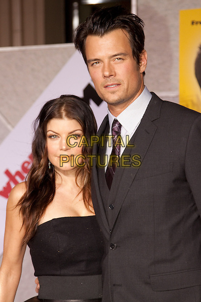 "FERGIE (STACY FERGUSON) & JOSH DUHAMEL .Arrivals - world premiere of ""When In Rome"" at the El Capitan Theater in Hollywood, Los Angeles, California, USA, 27th January 2010..half length black suit purple tie strapless dress couple married husband wife grey gray .CAP/ADM/RAT.©Ratianda/AdMedia/Capital Pictures."