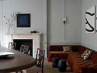 In the grey panelled dining room an L-shaped banquette is upholstered in brown velvet