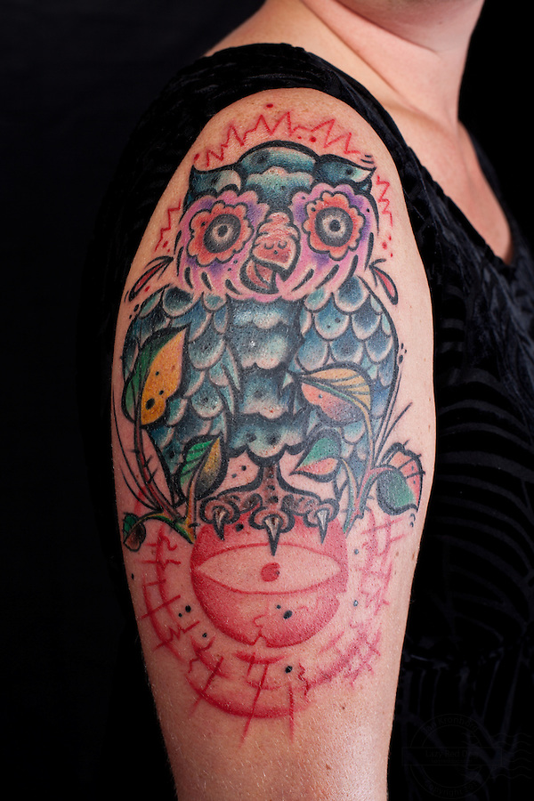 Danish woman with owl tattooed on right shoulder and the third eye on lower right arm.<br />