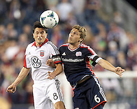 D.C. United midfielder John Thorrington (8) and New England Revolution midfielder Scott Caldwell (6) battle for head ball.  In a Major League Soccer (MLS) match, the New England Revolution (blue) defeated D.C. United (white), 2-1, at Gillette Stadium on September 21, 2013.