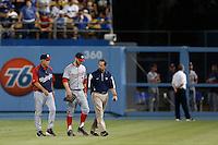 Bryce Harper #34 of the Washington Nationals returns to the dugout with Nationals Manager Davey Johnson and Nationals trainer Lee Kuntz after colliding with the right field wall during a game against the Los Angeles Dodgers at Dodger Stadium on May 13, 2013 in Los Angeles, California. (Larry Goren/Four Seam Images)