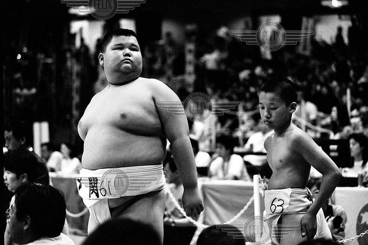 Two Young Rikishi Sumo competitors wait for their contest. 450 children, aged between 11-14, qualified for the All Japan Wanpaku Sumo Tournament held at the Ryogoku Kokugikan Stadium.
