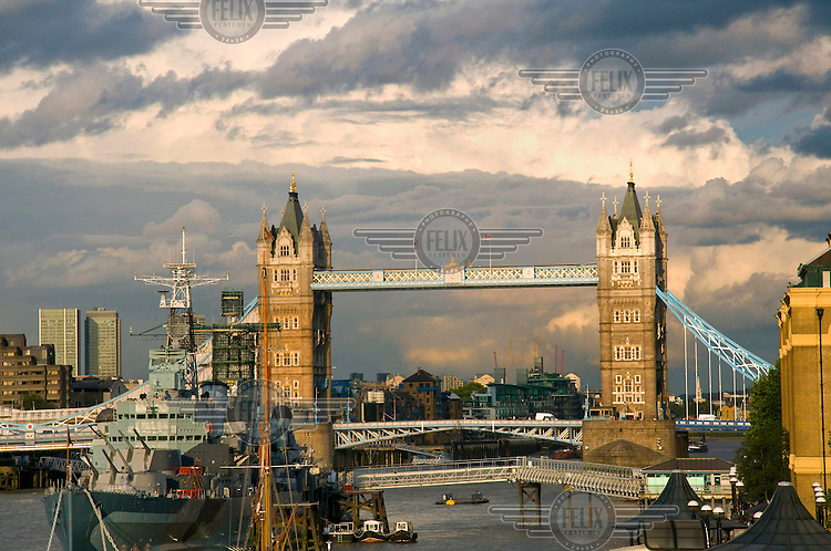 A view down the river Thames, looking at Tower Bridge and a warship.