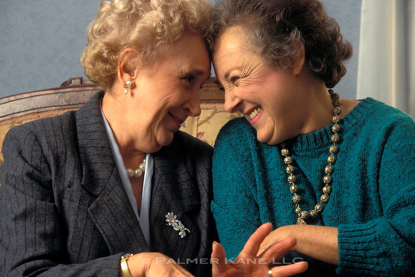 Two senior female friends laughing and gossiping