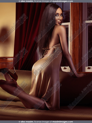 Beautiful glamorous african american woman posing on a couch at a window in a house