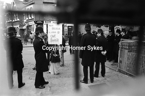 """Grunwick Strike North London UK. South Asian woman striker behind a banner that reads """"YOUR PAY RISE IS PAID BY OUR BLOOD. Taken from inside the factory gates during camera film processing factory strike."""