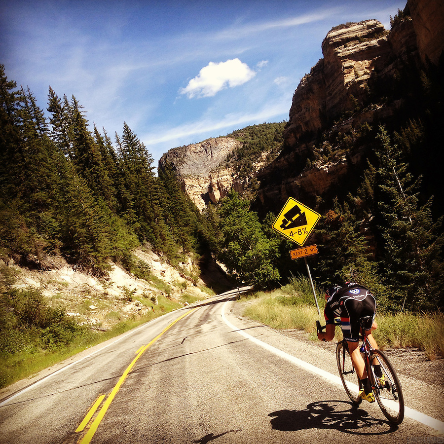 A lone cyclist descends Cedar Canyon, near Cedar Breaks National Monument, into Cedar City, Utah.