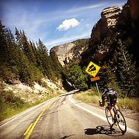 A lone cyclist descends Cedar Canyon, near Cedar Breaks National Monument, into Cedar City, Utah.