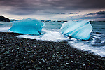 Glacial ice from Breiðamerkurjökull sits on the beach  of the coast at Breiðamerkursandur, Iceland, also known as the Jokulsarlon.