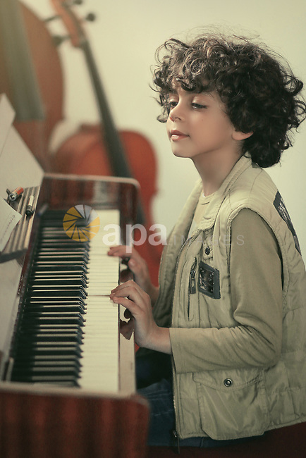 A boy plays on piano. Photo by Sanad Ltefa