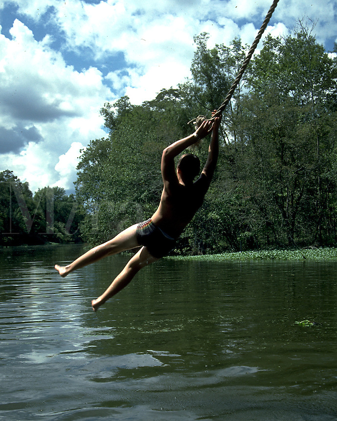 A child swings out and into a swimming hole in the bayou on a summer day. Louisiana.