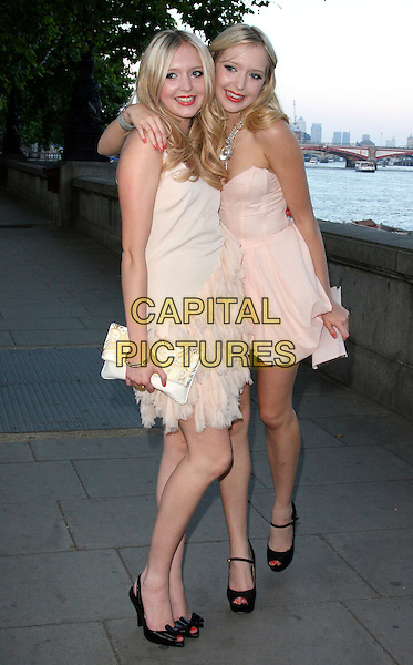 SAM & AMANDA MARCHANT .Samantha & Amanda Marchant Birthday Party arrivals at Temple Pier, London, England..June 25th, 2009.full length samanda sisters siblings twins pink white cream strapless dress feather clutch bag black sandals arm over peach shoulder hug embrace .CAP/ROS.©Steve Ross/Capital Pictures.