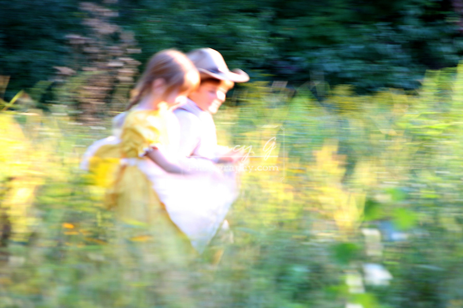 Children running through a field of flowers blurred intentionally