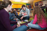 Salve Regina volunteer Jake Williams, '15, center, and Alannah O'Rourke, left, work with children on language skills at the Pell School in Newport as part of a Modern Languages Program.