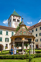 "Italy, South Tyrol (Trentino - Alto Adige), Neustift (Novacella) near Bessanone in Valle Isarco: Augustinian monastery (Abbazia di Novacella) - courtyard with ""fountain of miracles"" and collegiate church 