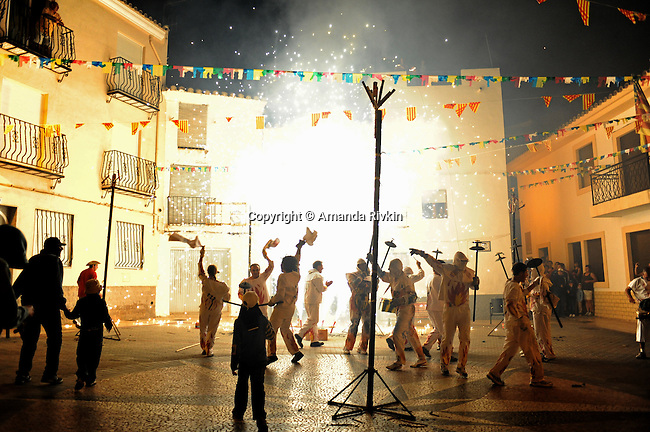 """A midnight pagan ritual, """"Corre Fuegos"""" or """"Running with Fire"""" concludes in the main square with a fireworks show after locals are chased through the streets by flame throwing and firework yielding men dressed in all white during the municipal fiestas in the town of Costur, Spain on August 17, 2009."""